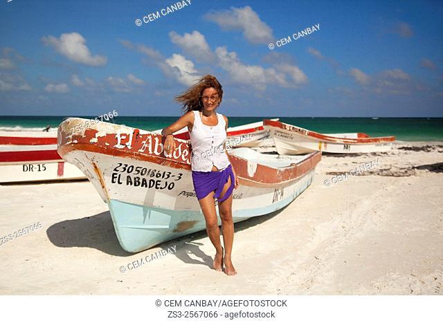 Woman posing near the fishing boats on the beach, Tulum, Quintana Roo, Yucatan Province, Mexico, North America