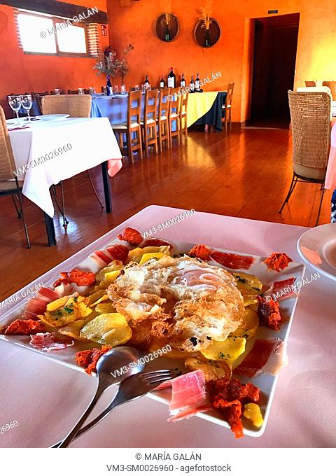 Fried eggs with potatoes and ham in a restaurant. Avila, Spain
