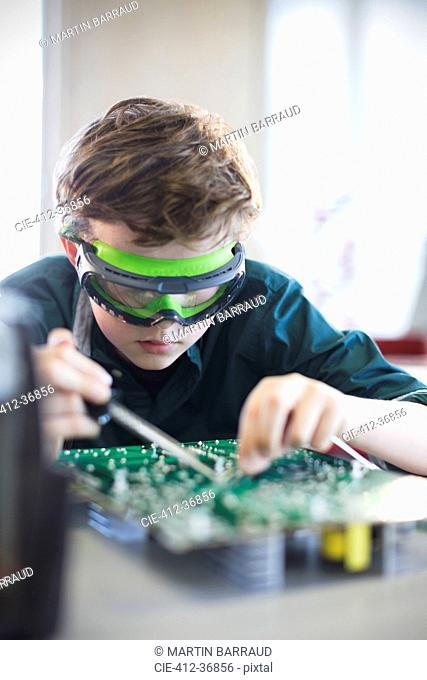 Focused boy student in goggles soldering circuit board in classroom