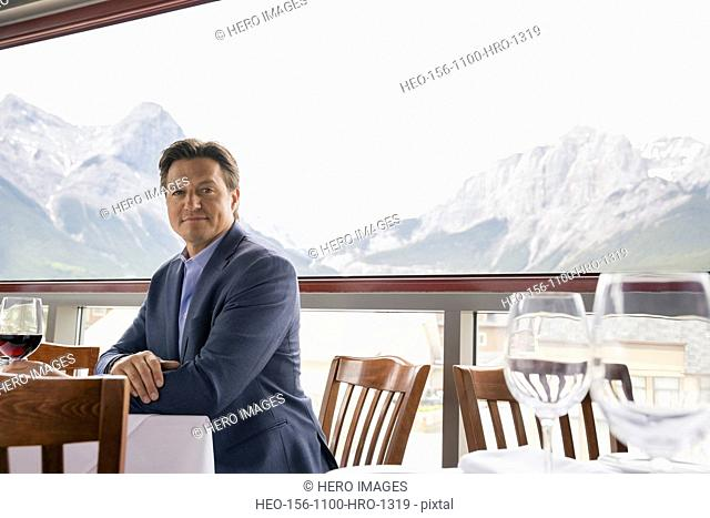 Portrait of confident businessman drinking wine on balcony