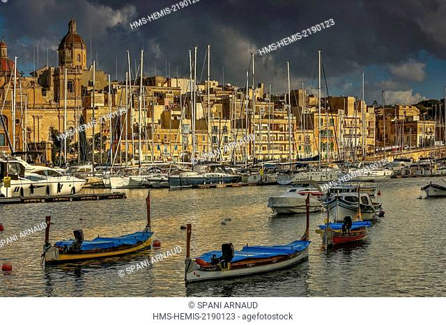 Malta, Birgu, Vittoriosa, general view of a yacht marina and a Mediterranean city at sunset, with traditional Maltese fishing boats in the foreground