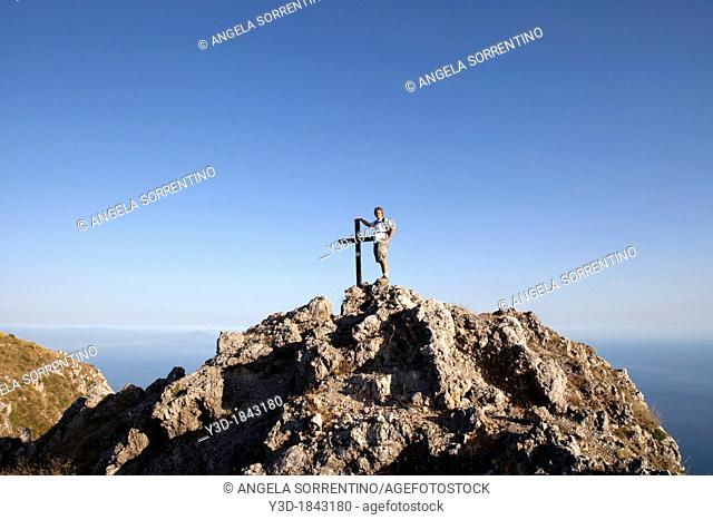 Mountaineer leaning on cross enjoying the view