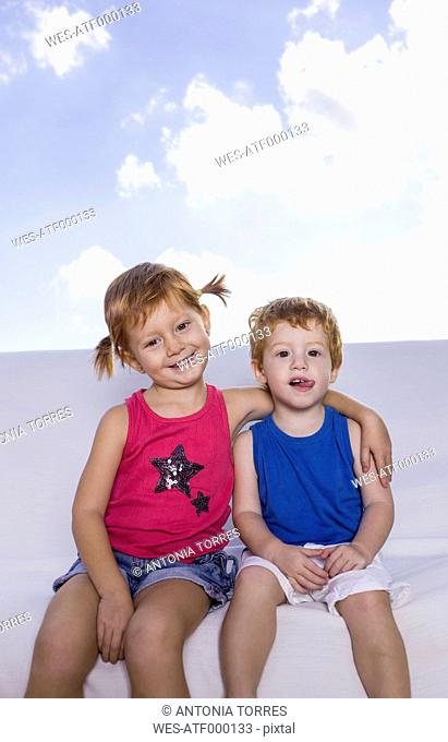Spain, Boy and girl sitting on white couch, smiling