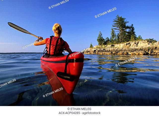A young woman paddles her kayak at sunset along the Lake Huron shoreline, Fathom Five National Marine Park, Ontario, Canada