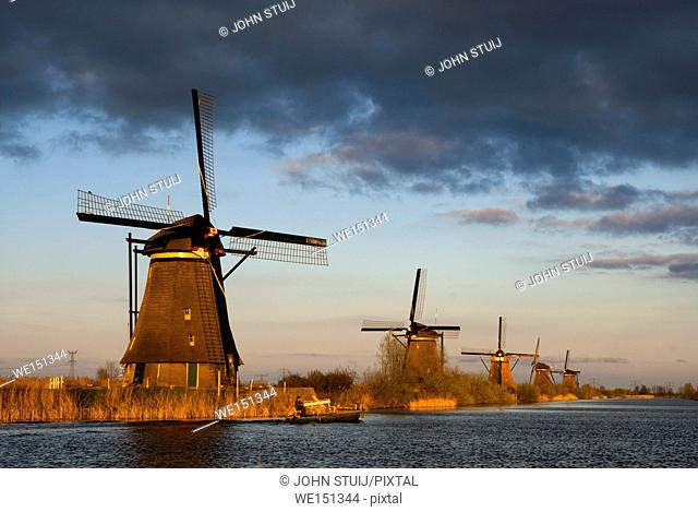 A boat sailing in the evening in front of the Kinderdijk windmills