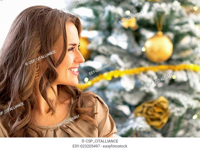 Profile portrait of young woman sitting near christmas tree