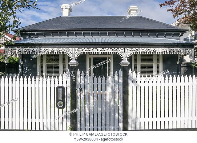 Classic late-Victorian era double-fronted timber home in suburban Elsternwick, Melbourne, Australia, displaying the characteristic picket fence, panelled door