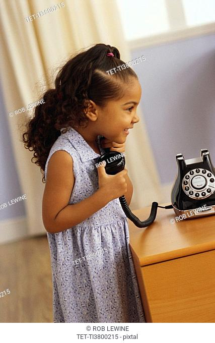 Young girl talking on telephone