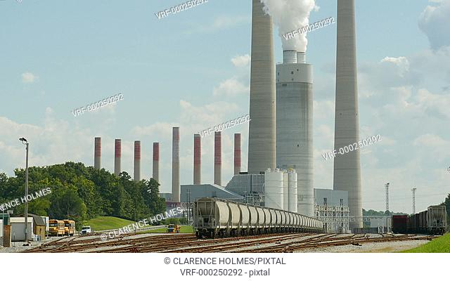 Hopper cars sit in the rail yard of the coal-burning Kingston Fossil plant as it emits steam through its chimney's as a by-product of electricity generation