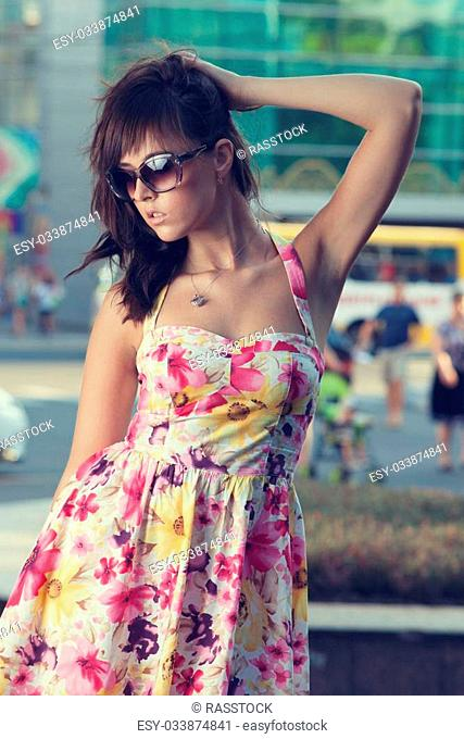 Beautiful model in sunglasses posing on urban background