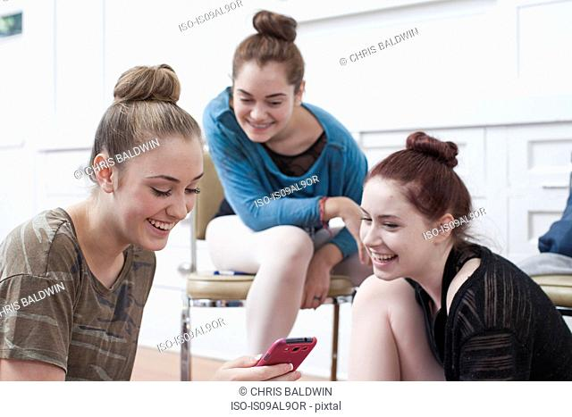 Three teenage girls reading smartphone message in ballet school