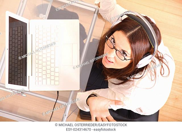 Business woman working on a Laptop while listening music with Headphones