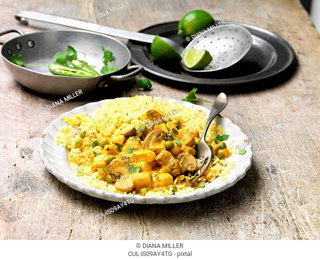 Food, vegetarian meals, paneer and cauliflower korma with pilau rice, green chilli, fresh lime, coriander, vintage bowl, wooden table