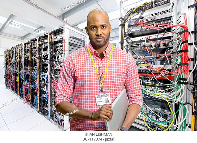 Portrait Of IT Technician In Data Centre Standing By Servers