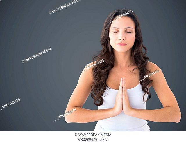 Woman meditating against grey background