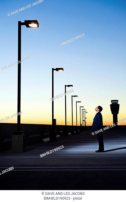 African businessman looking at street lamp in parking lot
