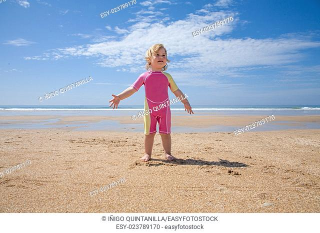 two years old blonde baby with pink and yellow swimsuit standing at golden sand beach seaside with ocean water asking or talking to, speaking