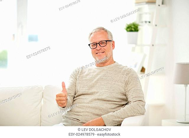 old age, gesture, retirement and people concept - smiling senior man in glasses showing thumbs up at home