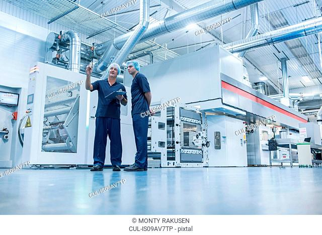 Workers with printing machine in food packaging printing factory
