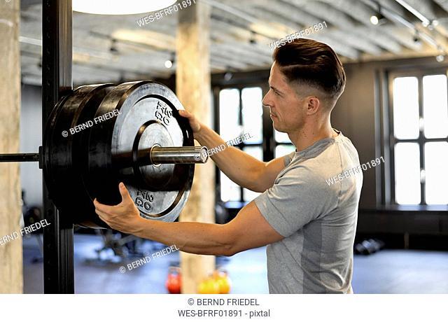 Man preparing weight at barbell at gym