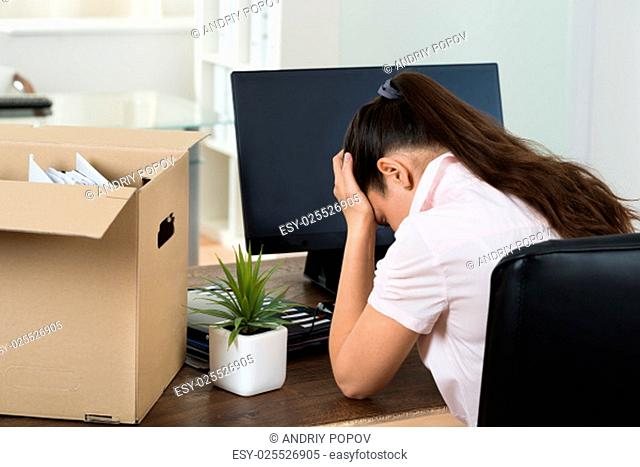 Dismiss Young Businesswoman With Belongings Sitting At Desk In Office