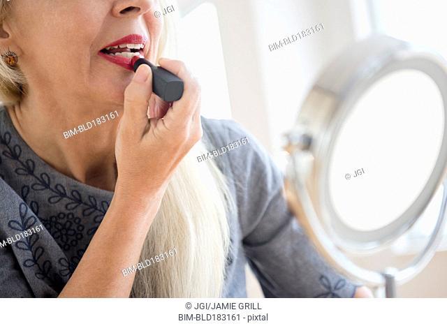 Caucasian woman applying makeup in mirror