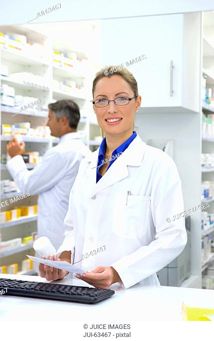 Pharmacist holding medication and prescription, smiling at camera from behind pharmacy counter