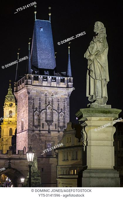 The statue of Philip Benizi de Damiani on the Charles Bridge with the Lesser Tower Gate in the background, Prague, Czech Republic, Europe