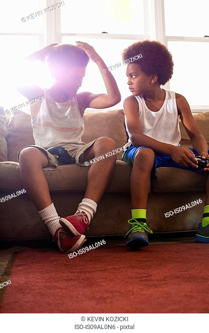 Two brothers with game controllers sitting on living room sofa