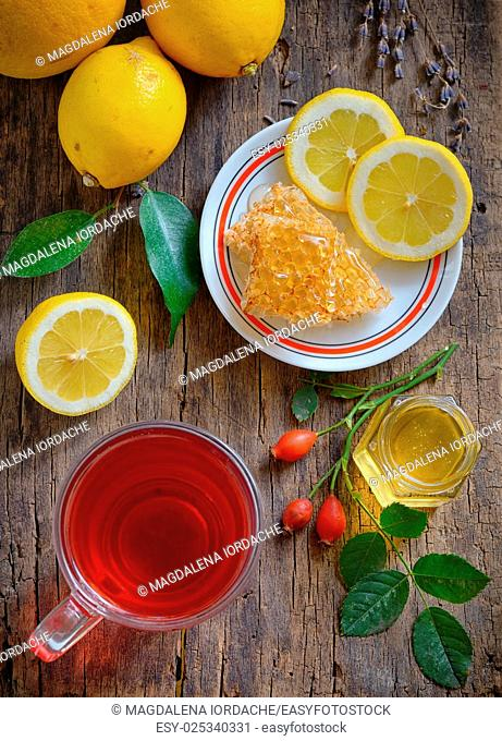 Tea with lemon and honey on wooden background