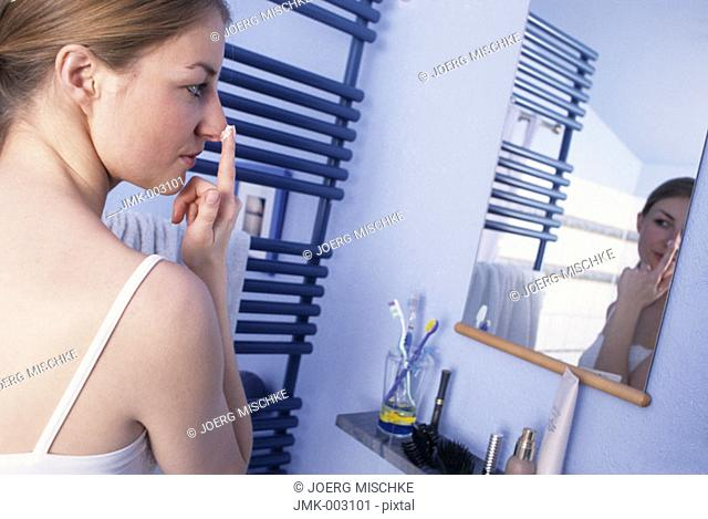 A young woman, 20-25 25-30 years old, in the bathroom, putting cream on her nose in front of a mirror