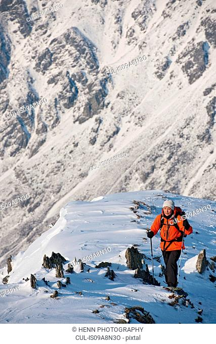 Female climber walking up snow covered ridge