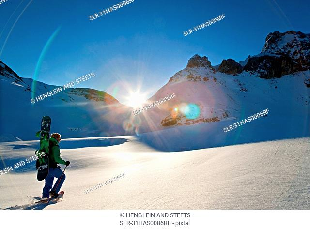Snowshoe walker at dawn with snowboard