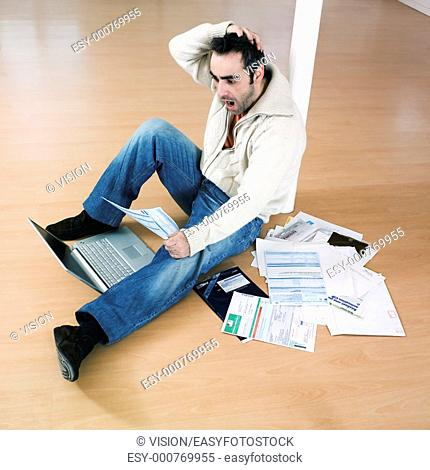 man sitting on the floor inside an empty loft appartement with tax forms and laptop computer