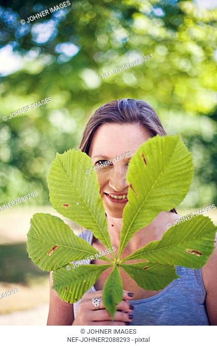 Portrait of smiling woman with chestnut leaf