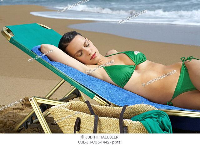 Young woman lying on beach chair with eyes closed
