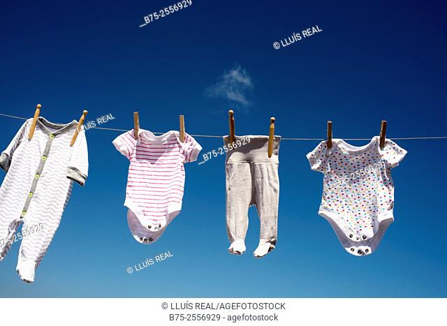 Baby clothes hanging in the sun with blue sky in the background