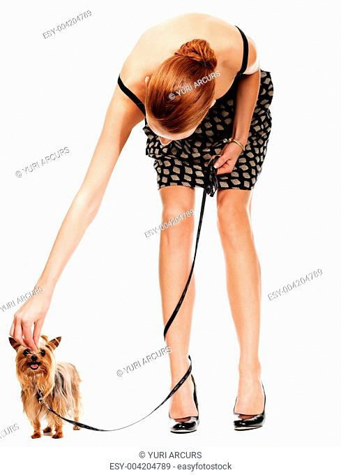 A young woman bending over to pet or tiny Yorkshire terrier