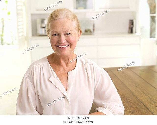 Senior woman smiling in kitchen