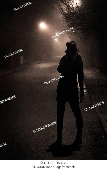 A person standing with top hat on a street