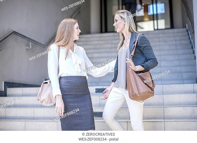 Two young businesswomen talking on the stairs