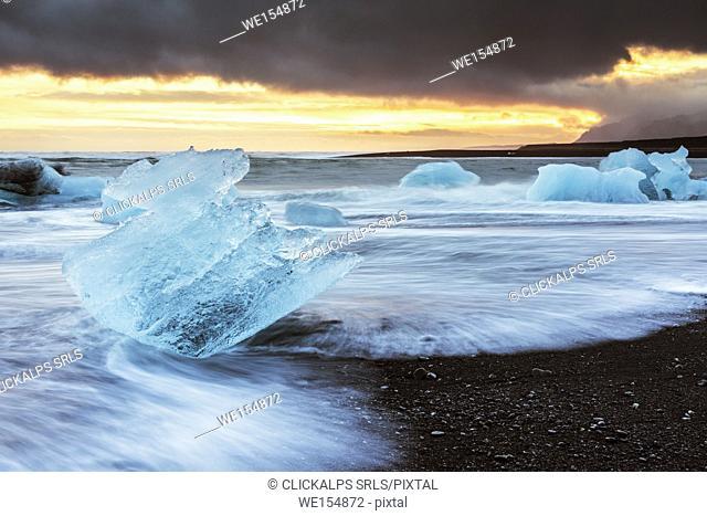 Jokulsarlon, eastern Iceland, Europe. Blocks of ice on the black beach in Jokulsarlon Glacier Lagoon during a sunset