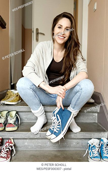 Smiling young woman sitting on staircase holding sneakers