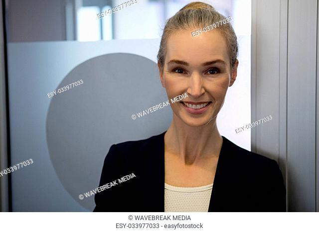 Portrait of smiling businesswoman standing by door