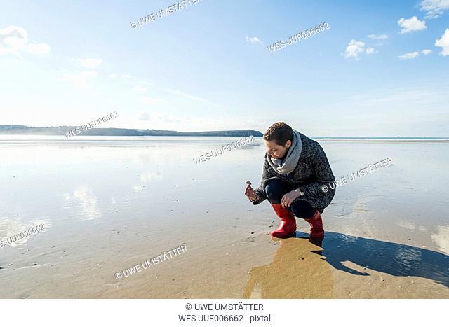 France, Bretagne, Finistere, Crozon peninsula, woman finding a seashell on the beach