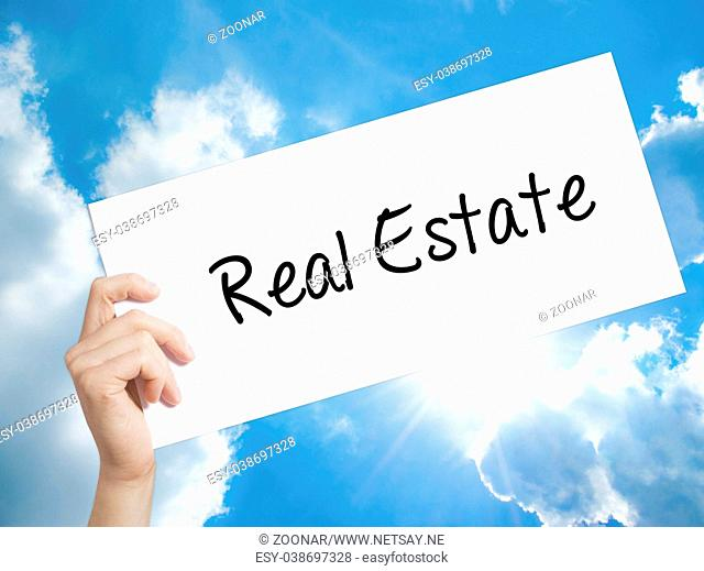 Real Estate Sign on white paper. Man Hand Holding Paper with text. Isolated on sky background