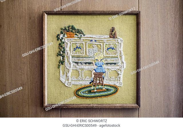 Framed Embroided Girl Playing Piano on Wood Panelled Wall