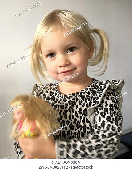 Portrait on a little blond girl with a toy, 2 1/2 years old, in Ystad, Scania, Sweden