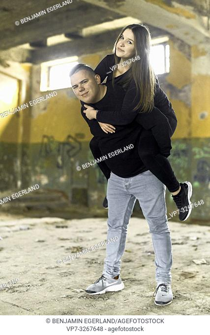 couple piggy back in house ruin, in Cottbus, Brandenburg, Germany