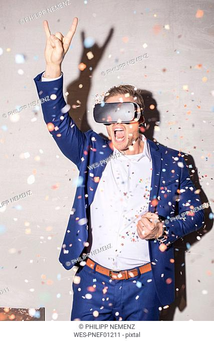 Screaming young man man with Virtual Reality Glasses standing in between confetti shower at a party